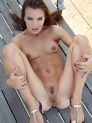Carina poses on a balcony and spreads her sweet pussy