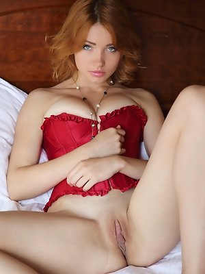 """Kika's bright red corset compliments her fair, porcelain smooth skin, highlighting her perfectly round breasts, slim waist, and smooth shav"